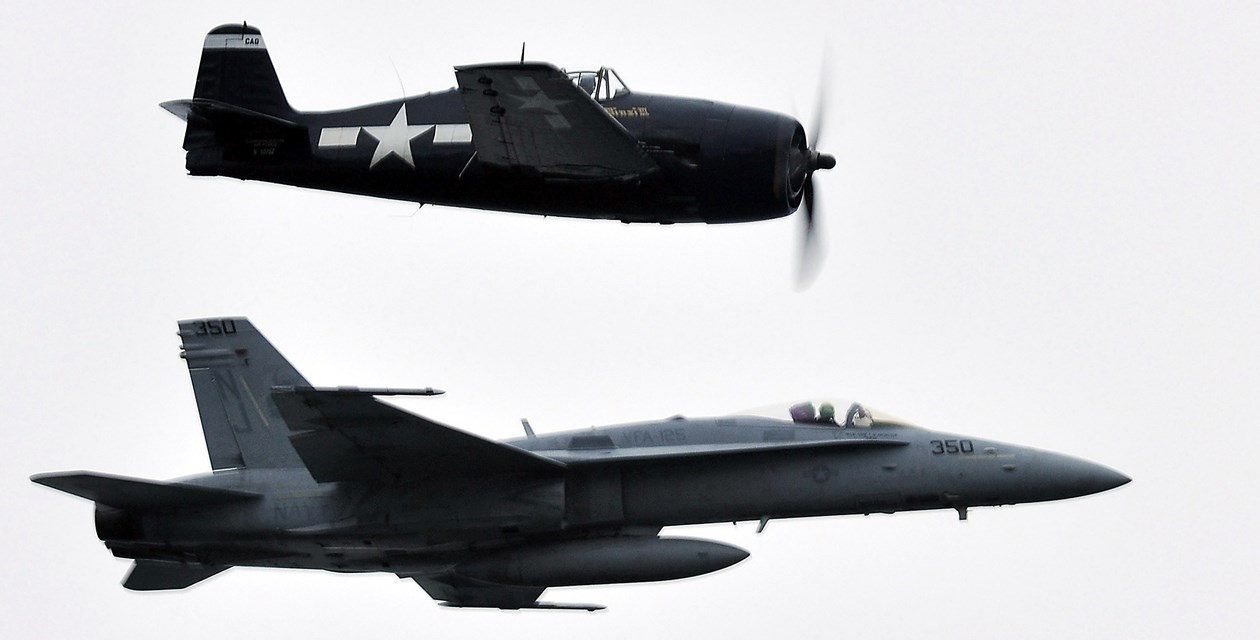 A WWII F6F Hellcat flies alongside an F/A-18C Hornet assigned to the Rough Raiders of Strike Fighter Squadron 125 during a Battle of Midway Commemoration ceremony aboard the USS Midway Museum. (U.S. Navy)