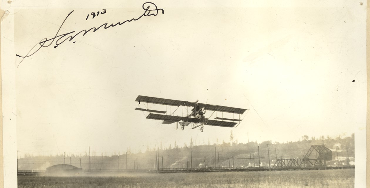 Blum-2 - Herb Munter's 1913 biplane with Maximotor engine flying above Harbor Island Field, Seattle, WA.