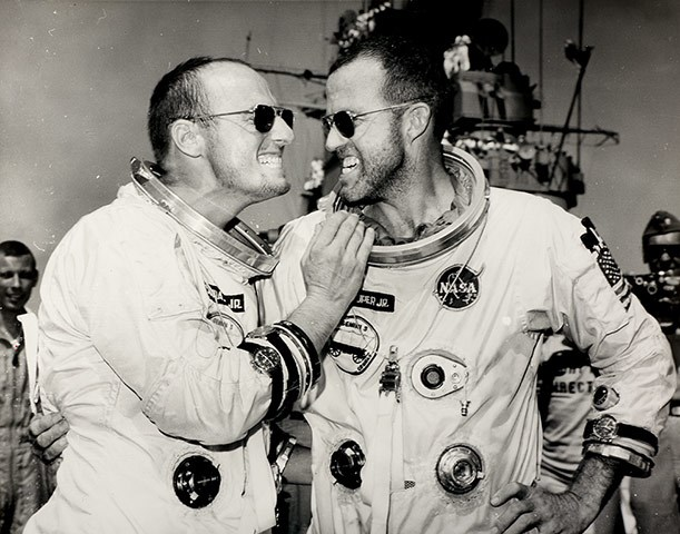 Pete Conrad and Gordon Cooper grin on the deck of the USS Lake Champlain -NASA